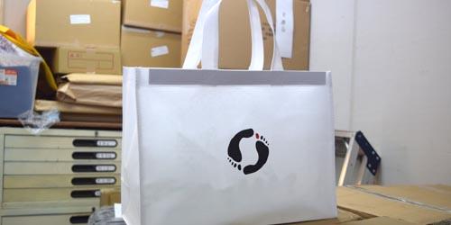 シューズショップでの販売持ち帰り用、 シンプルな作りの手提げ不織布バッグ