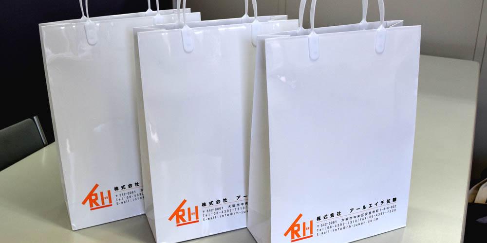 不動産会社向けの資料配布用紙袋で、PP加工+プラ製の持ち手のシンプルな仕様。