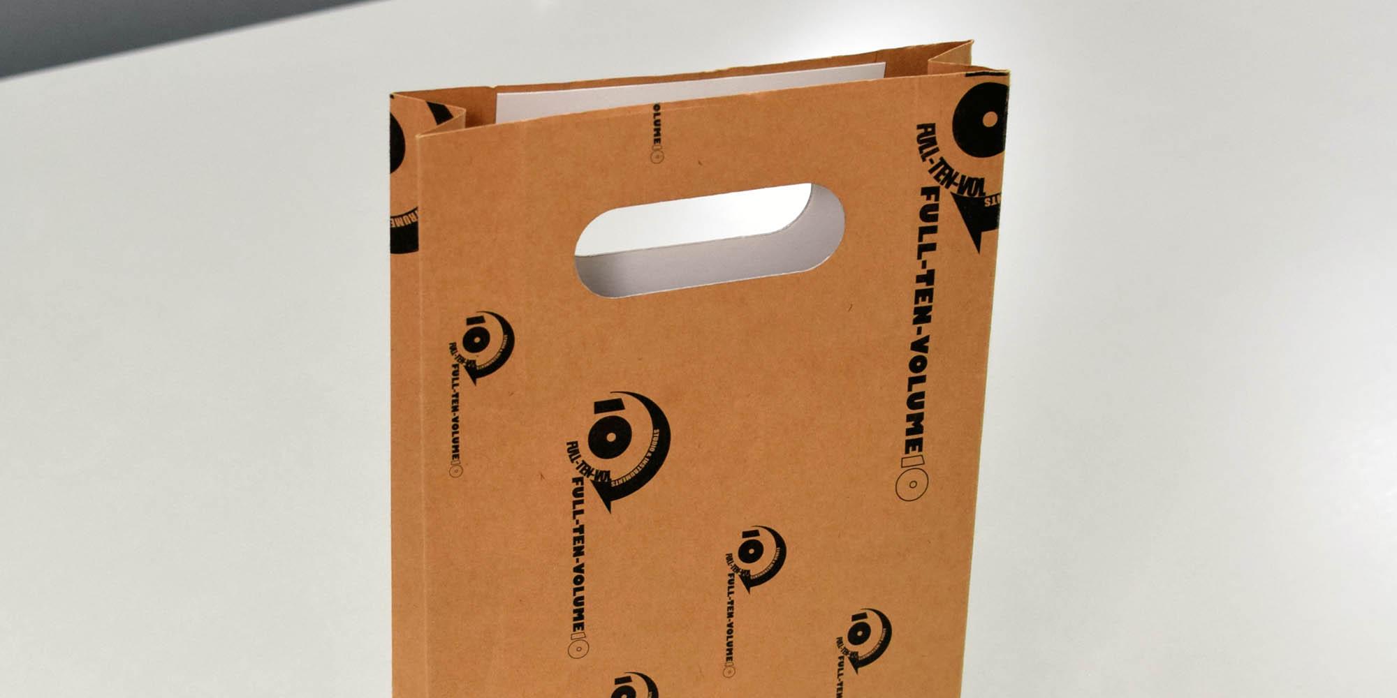 アパレルショップの小型商品持ち帰り用紙袋。珍しい小判穴の持ち手でレトロな仕上がり。